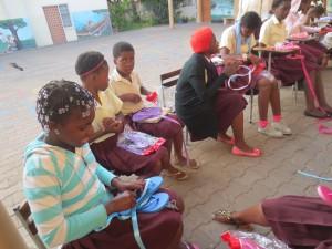 De meisjes versieren slippers die met winst verkocht worden op de markt. Zo hebben ze een kleine bijverdienste.